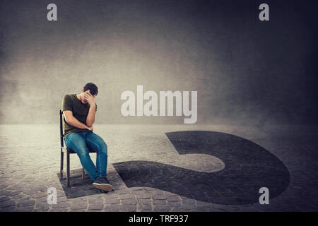 Decision making and life questions as a thoughtful anxious man, seated on a chair in a dark room, hold hand to forehead casting huge interrogation mar - Stock Photo