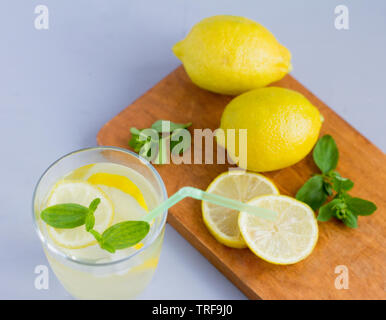 water in a glass with lemon and oregano leaves,a refreshing soft drink to quench your thirst in the heat and maintain tone - Stock Photo