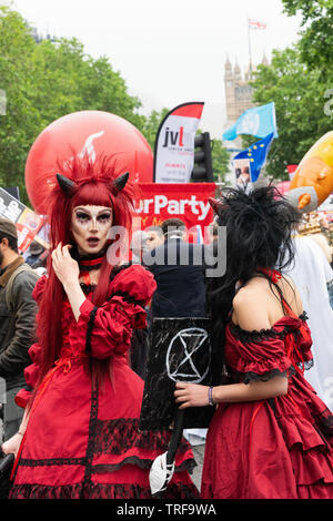 4th June 2019. London, UK. Anti Trump rally in Westminster. A woman in devil costume holds Extinction Rebelion placard at Trump protest. - Stock Photo