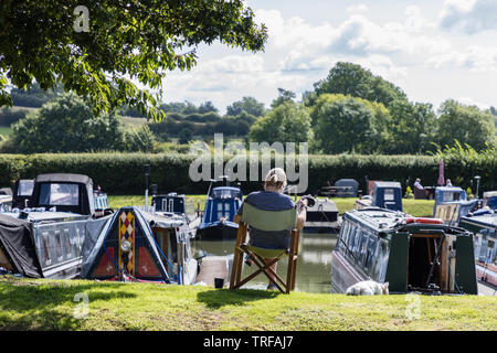 In a marina with canal narrowboats, a woman, with her back to us, sits in a folding wooden chair reading a newspaper whilst holding a dog on a lead. - Stock Photo