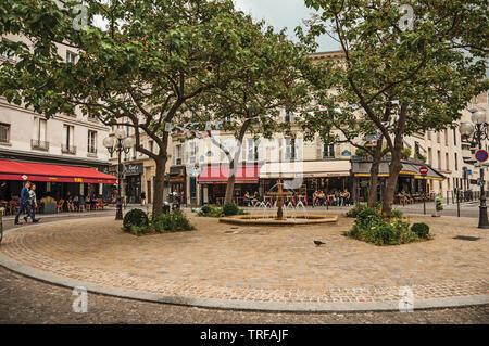 Small square with fountain, trees and restaurants in the Quartier Latin at Paris. One of the most impressive world's cultural center in France. - Stock Photo