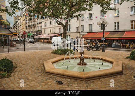 Square with fountain, trees and restaurants in the middle of the Quartier Latin at Paris. One of the most impressive world's cultural center in France - Stock Photo