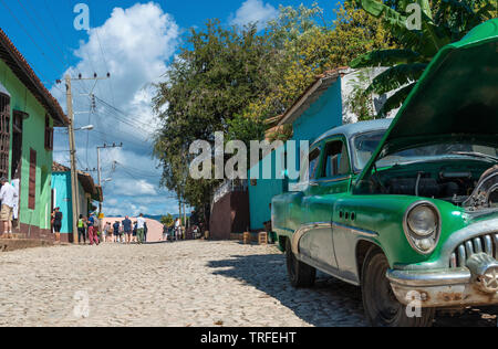 Classic American green car awaiting repair on one of the cobblestone streets in the old colonial town of Trinidad, Sancti Spiritus, Cuba, Caribbean - Stock Photo