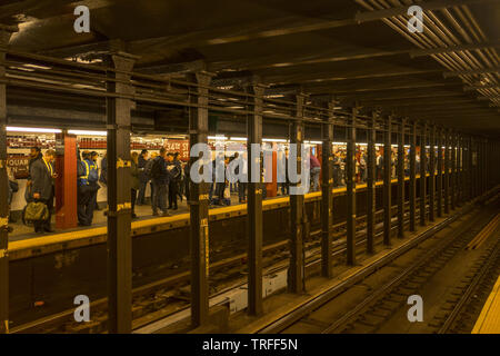 People waiting for a subway train at the 34th Street Penn Station stop in Manhattan. - Stock Photo