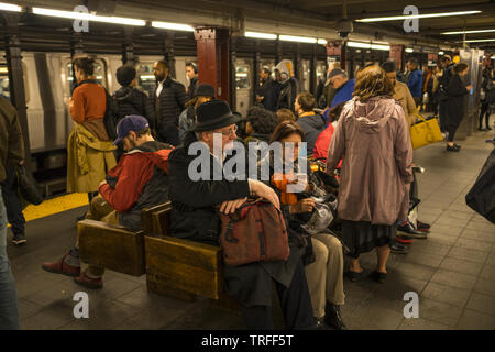 People wait for subway trains at  34th Street, Penn Station  in Manhattan, NY City. - Stock Photo