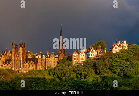 View of The Mound, St Giles Cathedran spire and Ramsay Gardens from Princes Street in dramatic low light, Edinburgh - Stock Photo