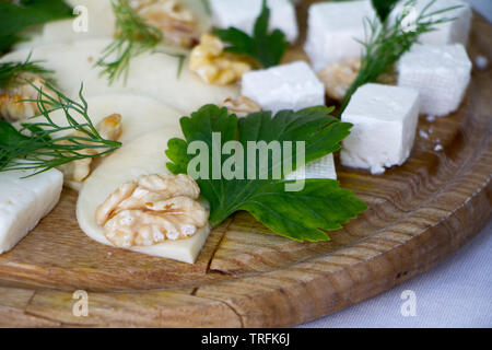 Extreme close-up of different types of cheeses, nuts, herbs and honey on a wooden board, the concept of a healthy snack, copyspace - Stock Photo