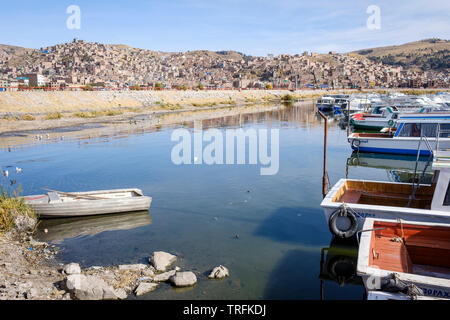Tourist boats docked in the morning on Muelle Lacustre at Puno Port on the Lake Titicaca with the city of Puno in the background, Puno, Peru - Stock Photo