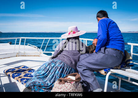 Local couple enjoying the views from the upper deck on a tourist boat tour at Lake Titicaca, Puno Region, Peru - Stock Photo