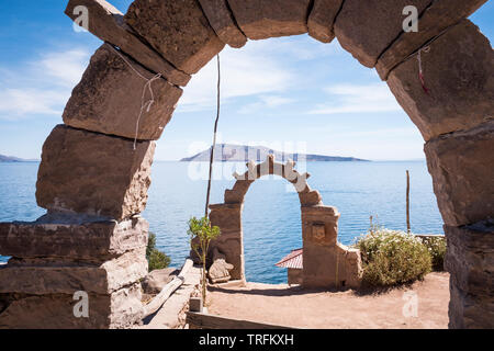General view of Amantani Island, seen from Taquile Island with traditional Taquile arches in the foreground, Lake Titicaca, Puno Region, Peru - Stock Photo