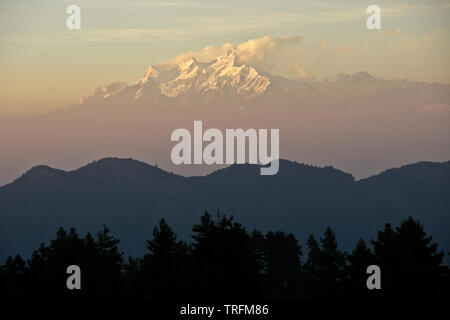 Foothills, valleys, and snow-capped peaks of Himalaya mountain range in late-afternoon light and mist, viewed from Daman, Nepal - Stock Photo