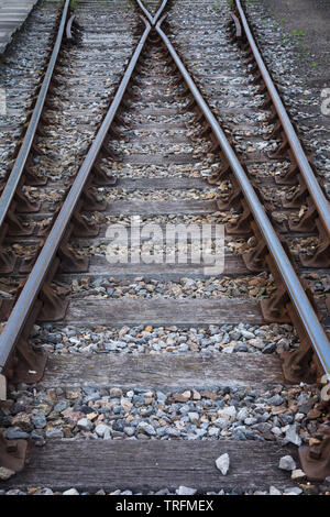 Perspective view of lines of hot rolled steel railway tracks, links, fasteners, sleepers and ballast at Didcot Railway Centre, Oxfordshire, UK - Stock Photo