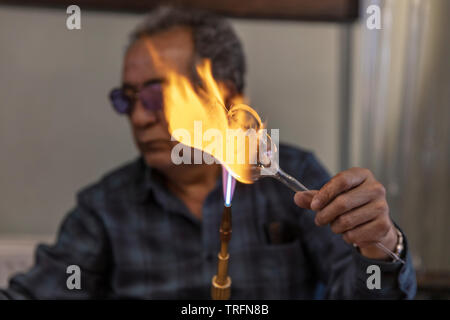 Close up macro of glass blower working with flame on a handmade wine glass from precious crystal in a workshop. Concept of handmade, high quality, art - Stock Photo