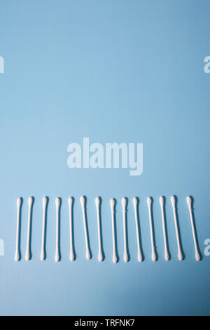 Cotton swabs in a line on a blue background - Stock Photo