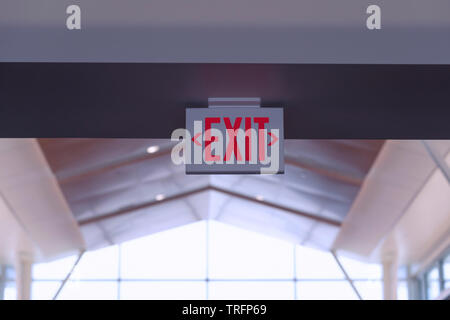 Exit Sign. Red Fire Escape Sign Hang on the Ceiling in the Airport. - Stock Photo