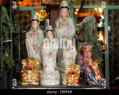 Figurines of the Goddess of Mercy, Kwan Yin / Kuan Yin and the God of Fortune, Cai Shen, at a Taoist / Daoist prayer items store - Stock Photo
