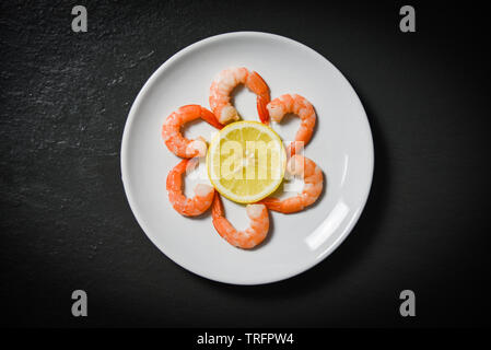 Shrimps prawns served decorate seafood plate and lemon on dark background - Stock Photo