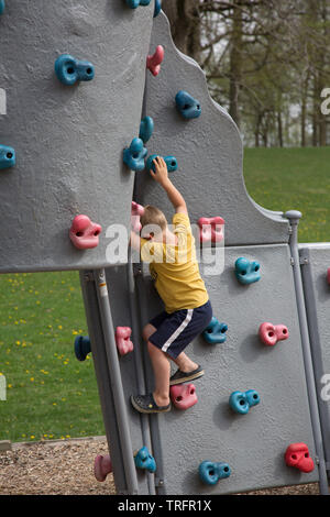 A young boy climbs the rock wall in the playground at Shoaff Park, a city park in Fort Wayne, Indiana, USA. - Stock Photo