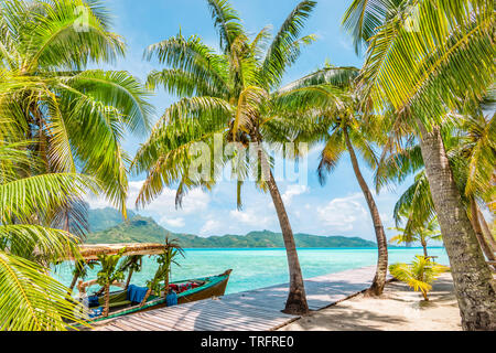 Beautiful landscape with coconut palm trees on tropical Island of Bora Bora. Decorated tourist boat moored at wooden quay. - Stock Photo