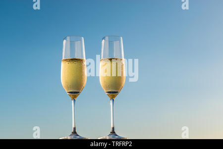 Golden champagne bubbles in flute glasses. Side view of two glasses of sparkling white wine isolated on blue sky background. - Stock Photo