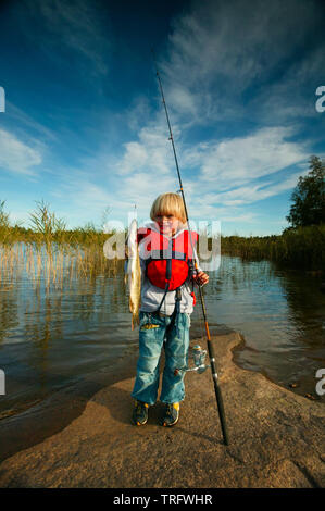 Young boy with his catch of Northern Pike, Esox lucius, in the lake Vansjø in Østfold, Norway. Vansjø is the largest lake in Østfold, and its surrounding lakes and rivers are a part of the water system called Morsavassdraget. September, 2006. - Stock Photo