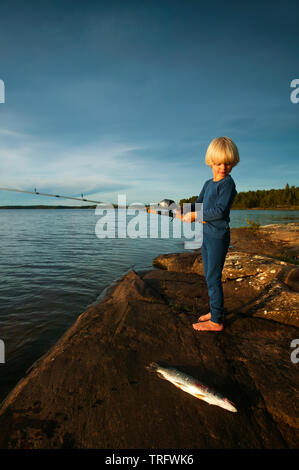 Young boy with his catch of Northern Pike, Esox lucius, in the lake Vansjø in Østfold, Norway. Vansjø is the largest lake in Østfold. The lake Vansjø and its surrounding lakes and rivers are a part of the water system called Morsavassdraget. September, 2006. - Stock Photo
