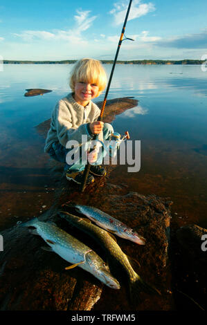 Young boy with his catch of Northern Pike, Esox lucius, in the lake Vansjø, Østfold, Norway. Vansjø is the largest lake in Østfold. September, 2006. - Stock Photo