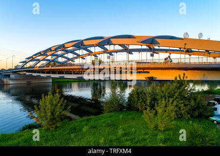 Suspension bridge Kotlarski  over the Vistula River in Krakow, Poland, in sunset light with unrecognizable cyclists. - Stock Photo