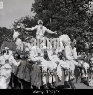 1950s, historical, On a hot summers day, a group of male morris dancers playing on a carnival float, with three of them taking a break from the dancing to enjoy a rest and a cigarette, England, UK. Morris dancing is a traditional English folk dance and an important part of summer fetes and carnivals, - Stock Photo