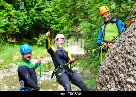 Thumbs up during an abseiling action in a rocky canyon - Stock Photo