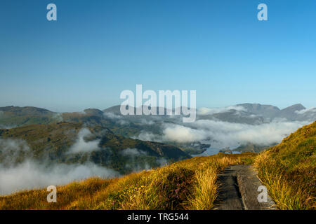Torc Mountain Trail footpath over the clouds on sunny day. The Reeks mountains in view at background. Killarney National Park, County Kerry, Ireland. - Stock Photo