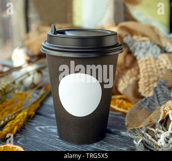 A paper cup of coffee is on the table with spikelets of cereal and slices of dried oranges on a sunny day - Stock Photo
