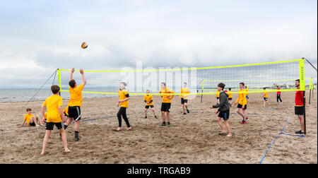 Ayr, UK, Scottish Volleyball Association organised the first school's beach volleyball competition held in Scotland, where 180 secondary school children, aged over 13 years, forming 40 teams from across the West of Scotland were invited to take part. The competition, won by  St Matthews Academy, Saltcoats (wearing yellow) was overseen by the members Scottish Volleyball Association who were hoping to identify potential future international team players and put them on a pathway to success. Credit: Findlay/Alamy Live News - Stock Photo