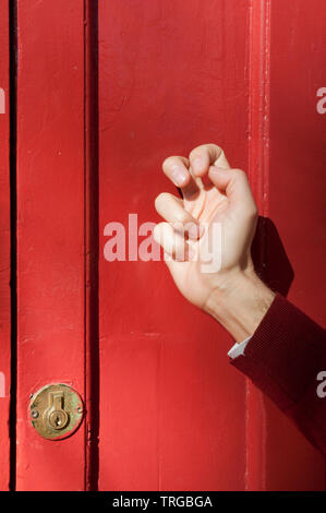 Man's hand tapping on a closed door with fingers. Close view. - Stock Photo