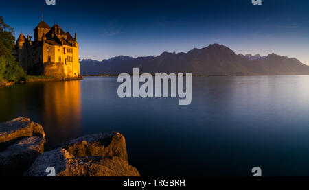 Montreux, VD / Switzerland - 31 May 2019: the historic Chillon Castle on the shores of Lake Geneva at sunset - Stock Photo
