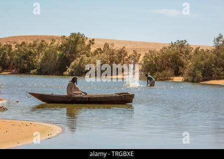 Fishermen from El Kab village in shallow water on lake Merowe drive fish into their nets by splashing the surface of the lake with long stakes - Stock Photo