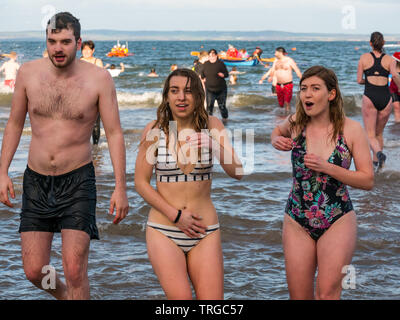 Loony Dook , New Year's Day: People brave cold water, Firth of Forth, North Berwick, East Lothian, Scotland, UK. Young women in swimsuits looking cold - Stock Photo
