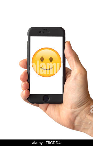 Smile emoji face on a smartphone screen - Stock Photo