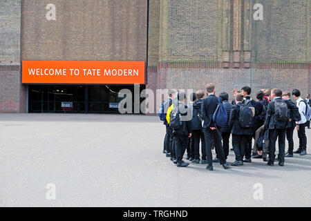 Group of school boys students pupils visiting the Tate Modern Art Gallery standing outside entrance to the building in London England UK  KATHY DEWITT - Stock Photo