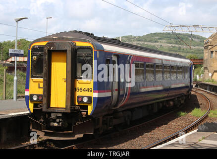Class 156 dmu, in old Scotrail Barbie livery with Scotrail branding removed, on Northern service at Carnforth with a passenger train on 3rd June 2019. - Stock Photo