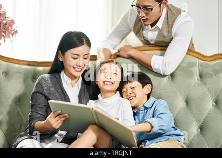 young asian parents and two children sitting on couch reading book together in family living room at home - Stock Photo