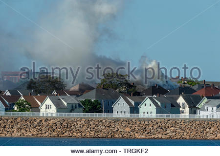 New Bedford, Massachusetts, USA - June 4, 2019: Smoke boils off roof of tenement and drifts across neighborhood during fire in South End of New Bedfor - Stock Photo