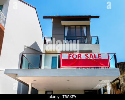 SINGAPORE, 15 MARCH 2019 - Low angle view front view of a house with red 'for sale' sign. - Stock Photo