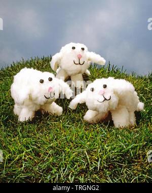 Three toy lambs on grass - Stock Photo