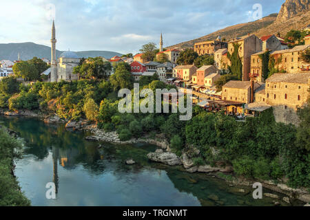 Golden hour over the Neretva river banks of the city of Mostar in Bosnia and Herzegovina seen from the famous bridge. - Stock Photo