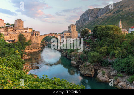 Evening scene in Mostar with the medieval town and the historic bridge over the Neretva river in Bosnia Herzegovina. - Stock Photo