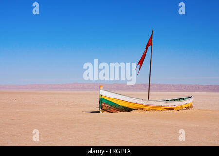 Small lonely wooden boat with red flag aground in the Chott el Djerid endorheic salt lake with mountain range at the horizon. Tunisia. - Stock Photo