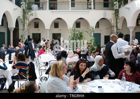 Tunisians having lunch at Fondouk El Attarine - a fine dining restaurant serving traditional Tunisian cuisine in the Medina of Tunis, Tunisia. - Stock Photo