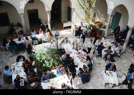 Tunisians having lunch at Fondouk El Attarine - a fine dining restaurant serving traditional Tunisian cuisine in the Medina of Tunis, Tunisia. - Stock Photo