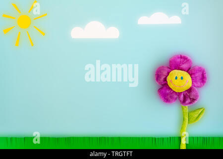 Paper sun, clouds, green grass and toy big flower with a smiling face on a blue background. Funny summer landscape composition with a luminous effect - Stock Photo